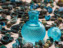 Blue glass bottle surrounded by dried plants. Close-up of filled blue glass bottle surrounded by dried plants on wooden surface. Cool fragrance concept Royalty Free Stock Image