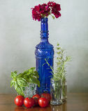 Blue glass bottle, vegetables and flowers Stock Images