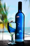 Blue glass and bottle of wine. Blue glass and bottle on wine on table with tropical beach in background. Exotic fish swimming inside bottle and glass Stock Image