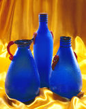 Blue Glass Bottles. On gold satin Royalty Free Stock Photo