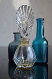 Blue Glass Bottles Antique Perfume Bottle. Two small blue glass bottles and an antique perfume bottle on reflective surface royalty free stock images