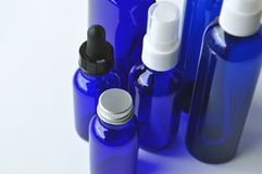 Blue glass bottles for cosmetic lotions, serums, oils. Dark blue glass bottles for cosmetic lotions, serums, oils and liquids with copy space royalty free stock images