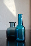 Blue Glass Bottles. Two small blue glass bottles on reflective surface stock images