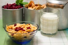 Blue glass bowl with cornflakes in front of old cups Royalty Free Stock Images