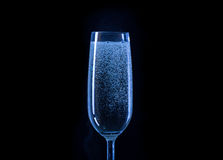 Blue glass of champagne on black background Royalty Free Stock Photos