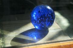 Blue glass crystal ball with bubbles. Magic sphere with light shing through the ball globe. Royalty Free Stock Photo