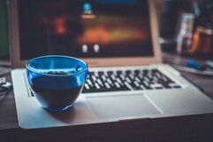 Blue Glass Cup on Silver Laptop Computer Royalty Free Stock Photos