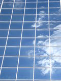 Blue glass facade reflecting white cloud Stock Photos