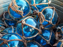 Blue Glass Fishing Floats. Glass fishing floats with rope knot netting piled in a bucket Stock Images