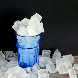 Blue glass full of ice water and ice cubes on a wooden table. Ice cubes all around. Black background Royalty Free Stock Photo