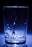 Blue glass get filled with water Stock Photo