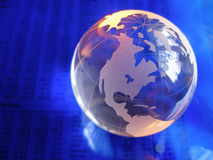 Blue Glass Globe. Glass globe on blue stock market and financial figures with orange highlights Royalty Free Stock Photos