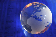 Blue Glass Globe. Glass globe on blue stock market and financial figures with orange highlights Royalty Free Stock Image