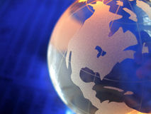 Blue Glass Globe Close. Close of glass globe on blue blurred figures in background with orange highlights stock photography