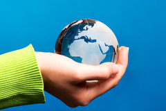 Blue glass globe in hand Royalty Free Stock Image