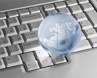 Blue glass globe on keyboard Royalty Free Stock Photo