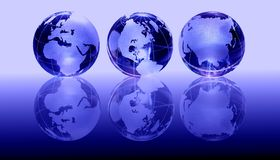 Blue glass globes. Three blue glass globes with reflections, on a gradient blue background Stock Photos