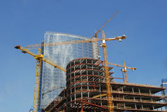 Blue glass high rise tower with a crane. On a bright blue sky Royalty Free Stock Photo