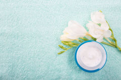 Blue glass jar with facial or body cream on the towel background. Blue glass jar with facial or body cream and flower on towel background Stock Image