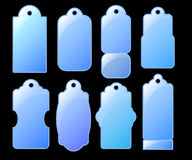 Blue glass-looking tags on black background. Winter seasonal  clipart. Royalty Free Stock Images