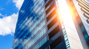 Blue glass modern business center in summer with sun behind Stock Photos