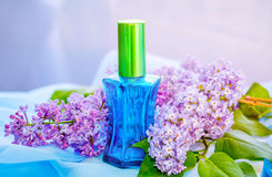 Blue glass perfume bottle and lilac flowers Royalty Free Stock Photography