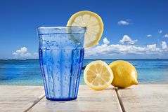 Blue glass with sparkling water and lemon Stock Photos