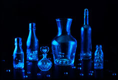 Blue Glass Still Life. Several blue glass bottles with beads and other glass bobbles on a black background Royalty Free Stock Photo