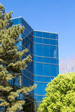 Blue Glass Tower Behind Green Trees. Under Blue Skies Royalty Free Stock Photos