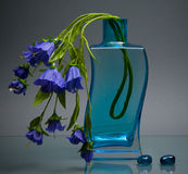 Blue glass vase with small flowers on gray Stock Photo
