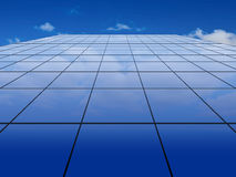 Blue glass wall on a sky background Stock Photos