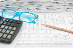 Blue glasses brown pencil and calculator on finance account. Blue glasses, brown pencil and calculator on finance account with pile of paperwork as background stock photography