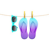 Blue glasses and flip flops hanging on rope with clothespins, isolated on white, summer background Royalty Free Stock Images
