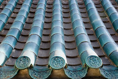 Blue glaze tiles. Several rows of blue glaze tiles with the ancient sculpture in front of the blue glaze tile .Photo shooted in China,2009.This kind of tiles are Stock Images