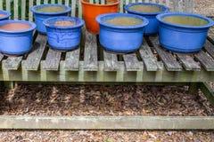 Blue glazed pots on open slat table, copy space Royalty Free Stock Image