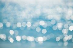 Blue Glitter. Defocused glittering lights at sea background stock images