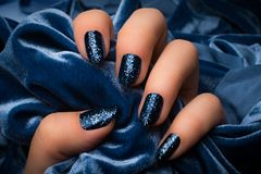 Blue glittered nails. The female hand with dark blue glittered nails is holding blue soft textile as blue textured background Royalty Free Stock Image