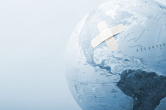 Blue globe with bandages stock photos