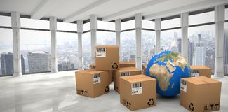 Composite image of blue globe with boxes. Blue globe with boxes against modern room overlooking city Royalty Free Stock Photo