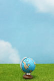 Blue globe on green grass over  blue sky background. Stock Photography