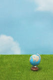 Blue globe on green grass over  blue sky background. Royalty Free Stock Photos