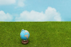 Blue globe on green grass over  blue sky background. Stock Photo