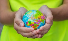 The Blue Globe in hands with the territories of the countries of the World on a green background. royalty free stock image