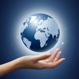 A blue globe held in hand Royalty Free Stock Images