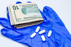 Blue glove, dollar bill, white drugs royalty free stock images