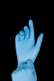Blue gloves. On a hand on a black background Royalty Free Stock Images