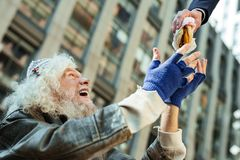 Homeless man wearing tattered blue gloves looking at food. Blue gloves. Homeless men wearing tattered blue gloves and old leather jacket feeling relieved while stock photo