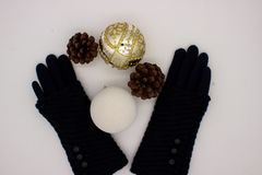 Blue gloves, white and golden Christmas balls and two pine cones on a white background. New Year's and Christmas Concept stock photos