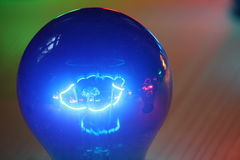 Blue glowing bulb. A blue colored bulb glowing and reflecting on a green and red background stock images
