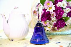Blue and gold Crystal bell on florals background. Tea times calling Stock Image